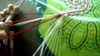 passaggio del filo colorato in un lavoro a tombolo