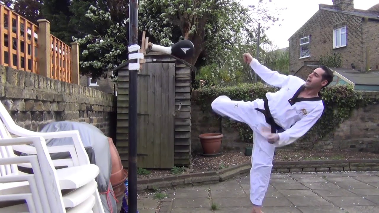 Practicing kicks on homemade Pad holder