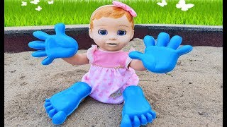 Dominika and doll play with hands toys and sand