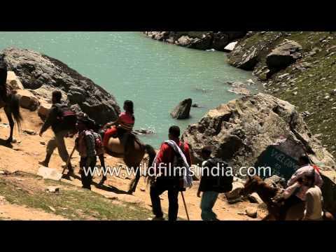 Devotees pass by Sheshnag Lake during Amarnath Yatra, Kashmir