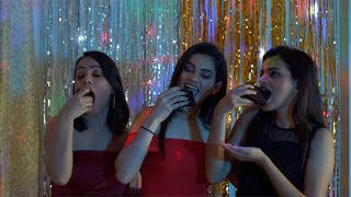 Pretty Indian girls eating delicious chocolate pastries at a New Year house party