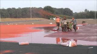 Aanbrengen rode kunststof korrels op atletiekbaan AV Spiridon