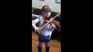Преподаватель музшколы учит девочку как правильно играть на скрипке