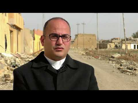 Fr Salar explains the need of help to rebuild houses in Batnaya village