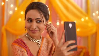 Gorgeous Indian woman smiling and checking her makeover while taking a selfie during the festival -  Technology concept