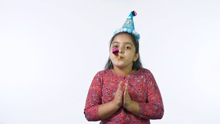 Cute little girl happily clapping and blowing noisemakers at a birthday party - leisure concept