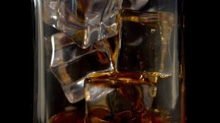Closeup shot of whiskey being poured into the ice-filled glass