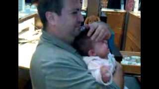 Baby getting ears pierced, Dad crying.