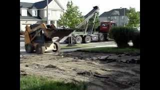 Removing asphalt from driveway with a bobcat
