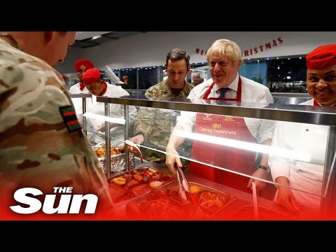 Boris Johnson serves Christmas lunch to British troops during a visit to a Nato mission in Estonia