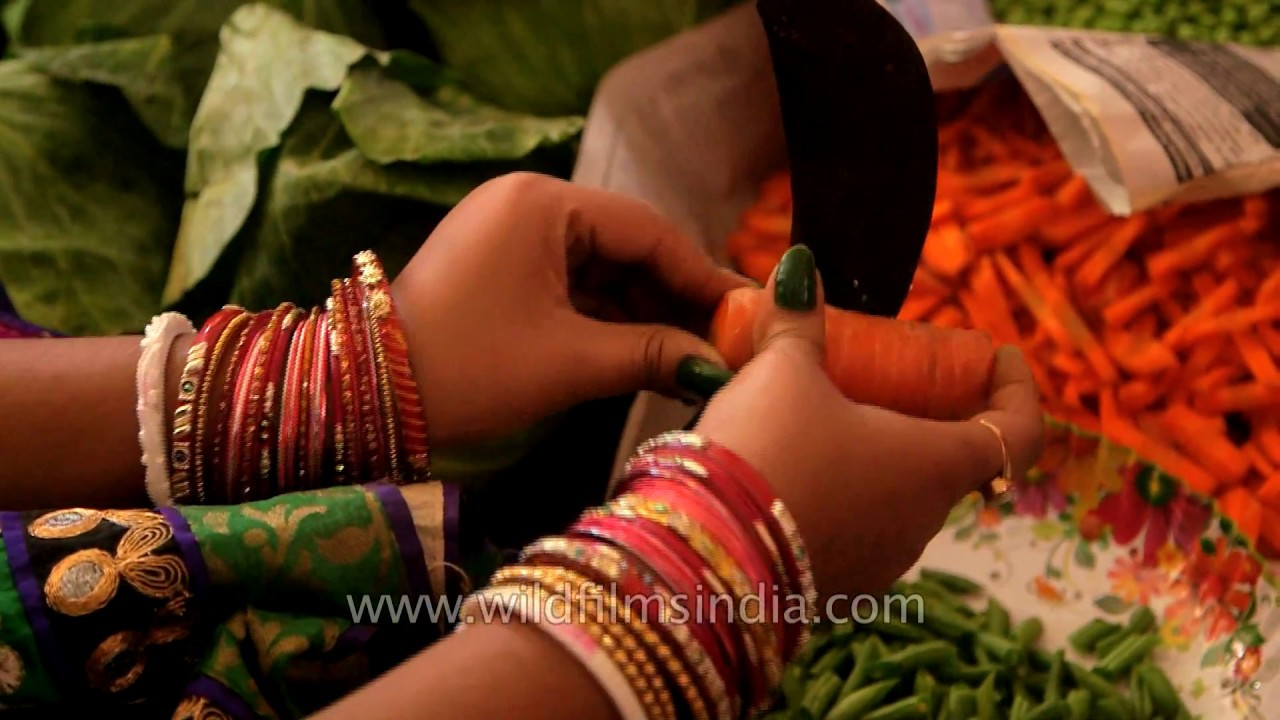 Women cut vegetables at a Bengali wedding in India, using a Boti or Dao