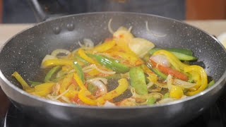 Sprinkling spices (red chili powder) while frying chopped vegetables in a non stick frying pan