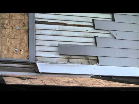 removing-old-asbestos-clapboard-siding-by-duct-taping-a-flat-prybar-to-an-extendable-painting-rod
