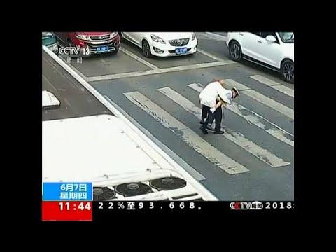 China policeman gives elderly man a piggy back