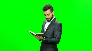 Man wearing a suit standing against the chroma screen reading book and giving expressions