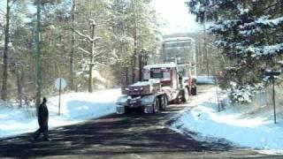 two dump trucks pulling a transformer up a hill   mammoet