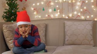 A disappointed little boy sitting alone on a couch for not having received his Christmas gift