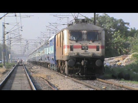 Horribly sun-burnt rusty brown WAP-7 with Mahakoshal Superfast gallops past Faridabad New Town