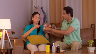 Indian husband giving medicine and glass of water to a sick wife - Medical Condition, Health Issue