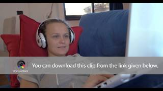 Woman in headphones with laptop on the sofa