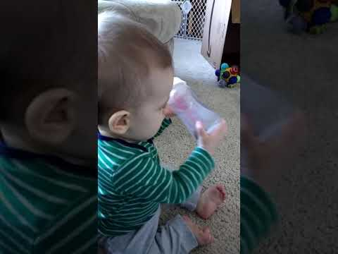 Nicholas playing with a penny bottle, seven months