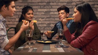 Group of four friends having delicious thin-crust pizza at an Italian restaurant