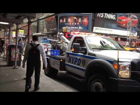 NEWER NYPD TOW TRUCK GIVING A CHARGE TO A NYPD TRAFFIC SUPERVISOR'S UNIT IN TIMES SQUARE,  NYC.