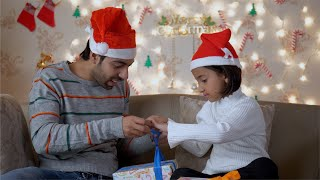 Indian father and daughter wrapping Christmas gifts and chatting
