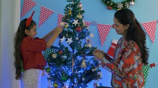 Cute Indian girl decorating Christmas tree with her mom during Christmas season