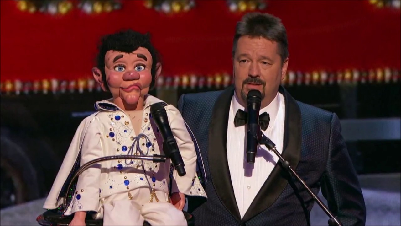 Terry Fator is holding his puppet in his right hand while performing on the stage