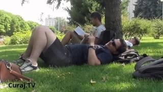 Mai mulți tineri stau pe iarba de la Guvern. Polițiștii și gardienii nu intervin