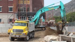 Blue Excavator loading dump truck