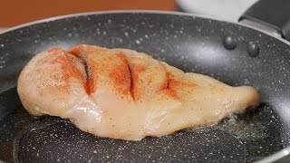 Putting raw chicken breast in a frying pan for cooking