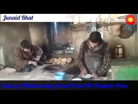 BAKERY WITHDRAWING BREAD FROM HIS TANDOOR OVEN AT BOTINGOO SOPORE  ( Sameer khandur)
