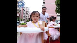 Chinese man creates spinning stroller for triplet daughters