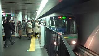 副駅名「大門・浜松町」の到着アナウンスが流れる都営大門駅に到着してたくさんの乗客が乗り込む大江戸線光が丘行き12-000形
