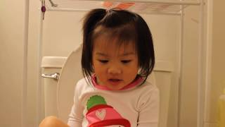Cute toddler using the toilet