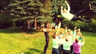 Подбрасывание жениха (молодого человека) гостями высоко вверх. Молодые люди танцуют на улице