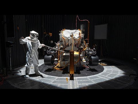 A person in protective clothing points a probe at the Mars rover in a cleanroom.