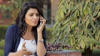 Beautiful girl standing outside in a park and arguing with someone on her mobile phone