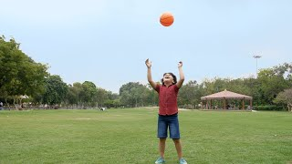 Young handsome kid happily playing with an orange ball - healthy and playful child