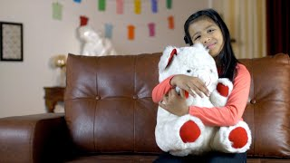 Closeup shot of a young charming girl playing with her toy teddy bear at home