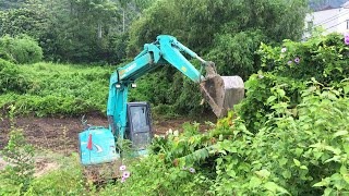Use An Excavator To Remove Wild Plants In The Forest