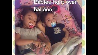 Babies fighting over balloon