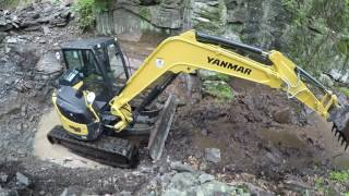 Hammering rock with an excavator