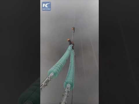 Hardworking Chinese: Electricians on power lines hundreds of feet above ground