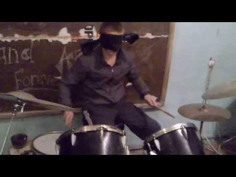 Пацан играет с завязанными глазами на барабанах