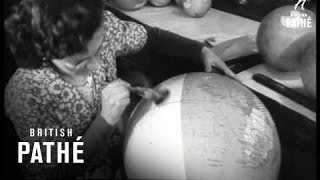 Globe making. Willesden, North West London. A man puts wet paper ar...
