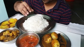 eating show rice with egg curry potato dum fried potato and tomato chatni