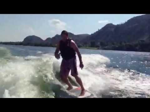 Guy drinks beer wakesurfing